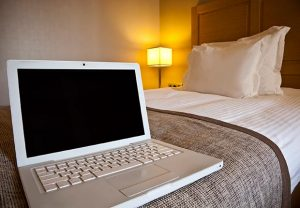 Laptop on hotel room bed